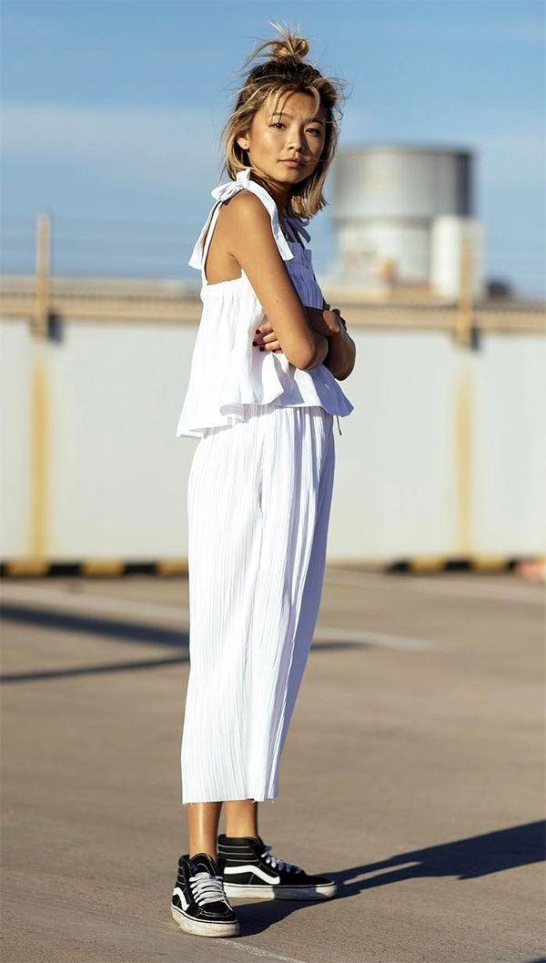 Street style look com macacão branco e tênis de cano alto, ótimo para dar um toque mais despojado ao seu look