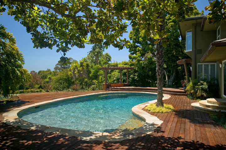 Kidney shaped pool with wood deck, pool stone coping, stairs and bench; blending natural colors of wood and stone.