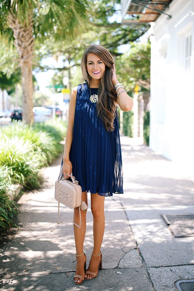 navy pleated dress with neutral accessories
