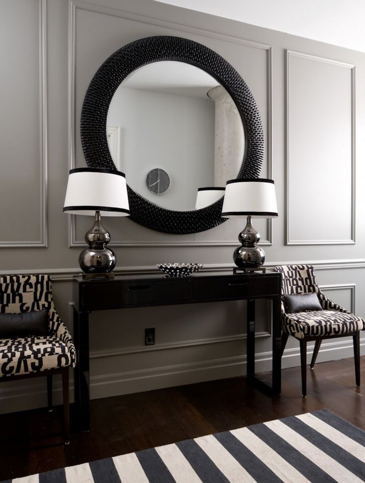 Black and white entryway with huge round mirror. A mirror also works to create the illusion of extra space by visually expanding a contained area. Just make sure that it is in proportion to the dimensions of the foyer. ➤ Discover the season's newest designs and inspirations. Visit us at http://www.wallmirrors.eu #wallmirrors #wallmirrorideas #uniquemirrors @WallMirrorsBlog