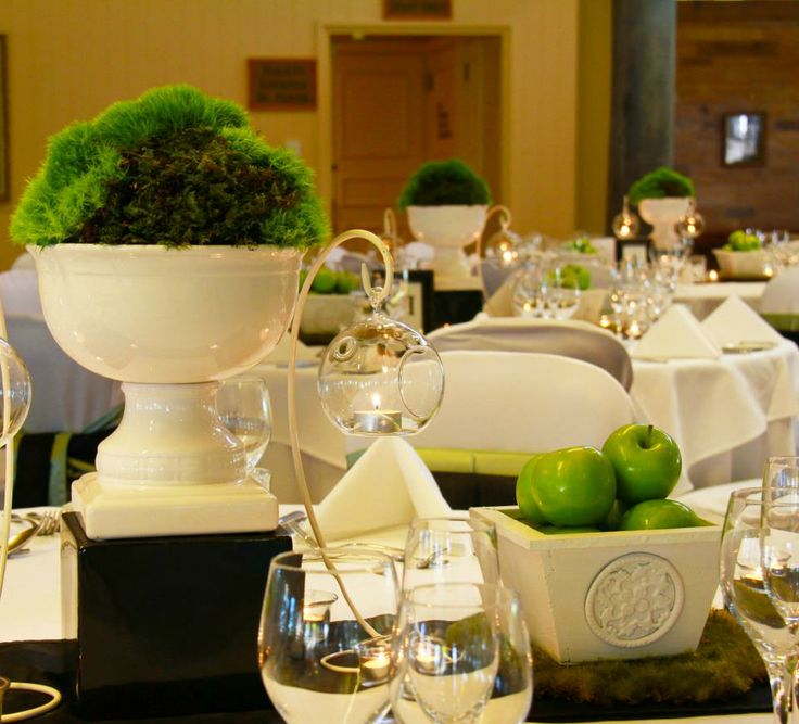 Green moss inspired centrepieces, chic white timber planters with fresh green granny apples, hanging glass tea lights, white votive candles and tea lights, moss matts and black satin stripe table runners