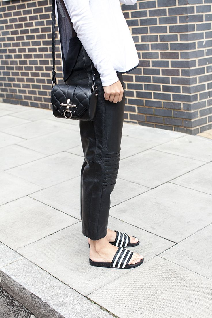 Charlie wears baggy leather trousers from her collection with Rag & Bone  top, Adidas slides and Givenchy bag.