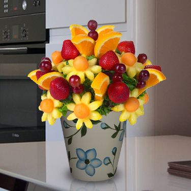 Daisy Pineapple With Orange - This edible fruit arrangement chocked full of orange slices, pineapple daisy flowers with cantaloupe, strawberries and grapes. A fruit arrangement sure to brighten someone's day! You can create your own edible fruit arrangements - www.VaaV.ca