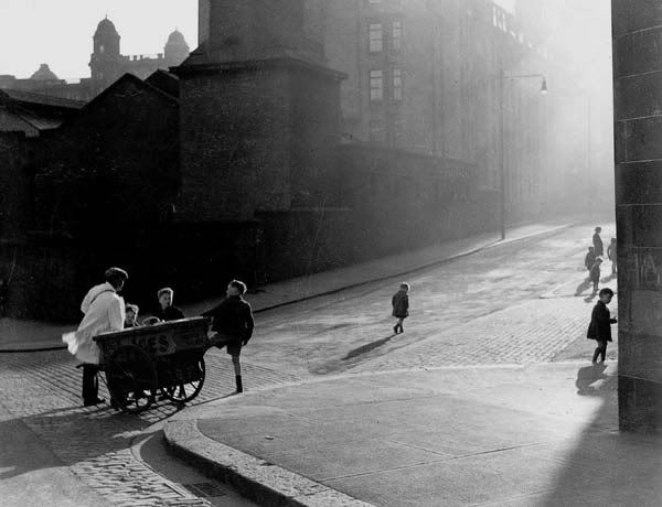 Gizzi, the ice-cream man, Glasgow. Guiseppe Gizzi, with his ice cream barrow at the corner of Wishart Street, James Orr Street and Glenfield Street, around 1937. His sales pitch covered miles of streets in Glasgow's east end where he pushed his barrow daily, switching in the winter to roasted chestnuts. The building behind the barrow is the boiler house of the Glasgow Royal Infirmary.