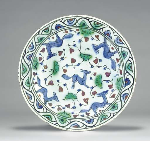 AN IZNIK POTTERY DISH  OTTOMAN TURKEY, CIRCA 1620  With sloping rim on short foot, the white interior painted in blue, black and green underglaze and red enamel with gambolling blue foxes amongst scrolling foliate motif, the border with undulating vine issuing blue and green leaves,   11in. (39.3cm.) diam.