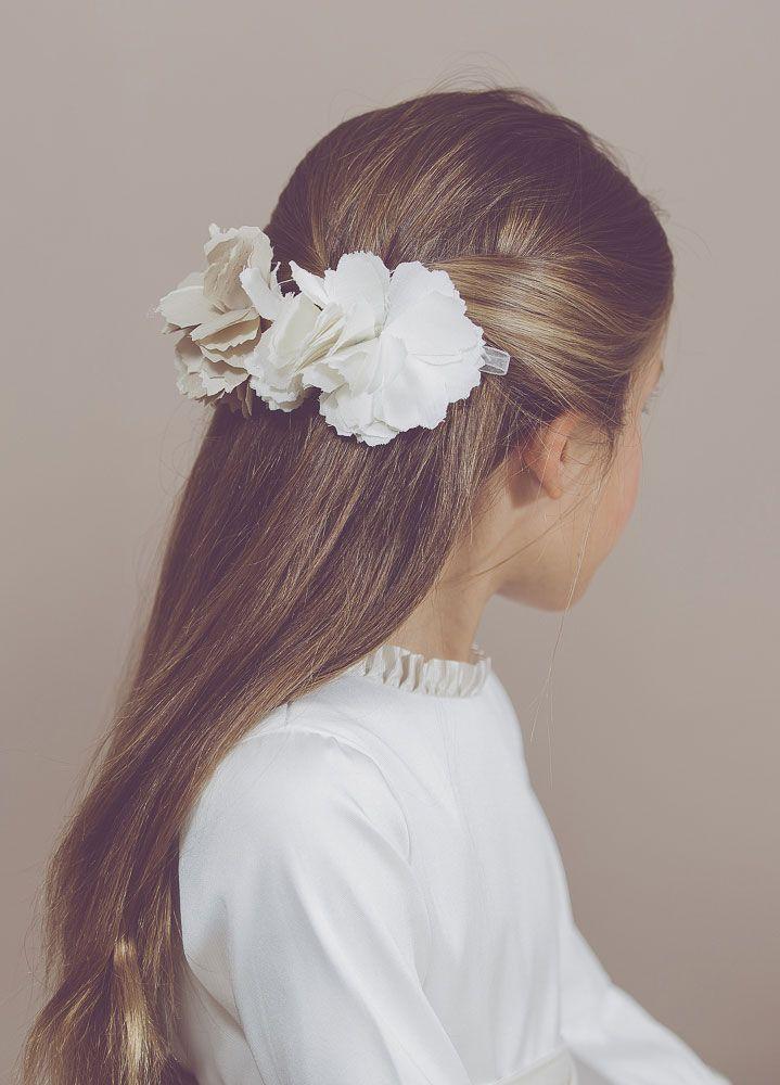 Otra idea perfecta para niñas con el pelo largo es recogerle los laterales de su melena en la parte de atrás con un pasador de gran tamaño con flores de un solo color o si sois más atrevidas de uno completamente diferente ¡vosotras decidís qué estilo os gusta más! Imagen cortesía de Coordinanos. - WomansDaySpain.es
