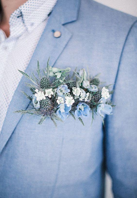 traje azul claro, una camisa estampada y un exuberante flor azul y flor en el ojal de cardo