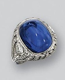 CABOCHON SAPPHIRE AND DIAMOND RING, CIRCA 1920. The cushion-shaped sugarloaf cabochon sapphire weighing approximately 22.00 carats, flanked by 2 pear-shaped diamonds, within delicately pierced shoulders further set with small old European-cut diamonds, mounted in platinum