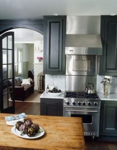 Black, dark grey painted cabinets with wood island accent and wood floors, light walls.