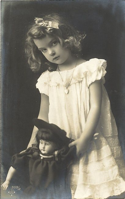 Haunting child | Vintage photo of hauntingly beautiful young girl with her doll, circa 1900 - 1925.