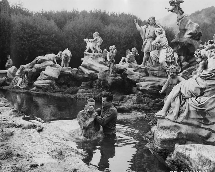 A US Army soldier is baptized by a chaplain in the fountain at the Palace of Caserta.
