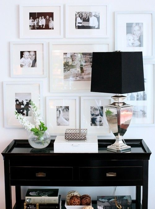 simple white gallery wall, black console, fresh flowers, and nickel lamp.  beautiful black and white vignette.