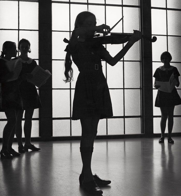Max Dupain has strikingly captured the silhouette of a young violinist rehearsing at the Methodist Ladies' College in Burwood, Sydney. This photograph was used by the Department of Trade to promote Australia's education system.
