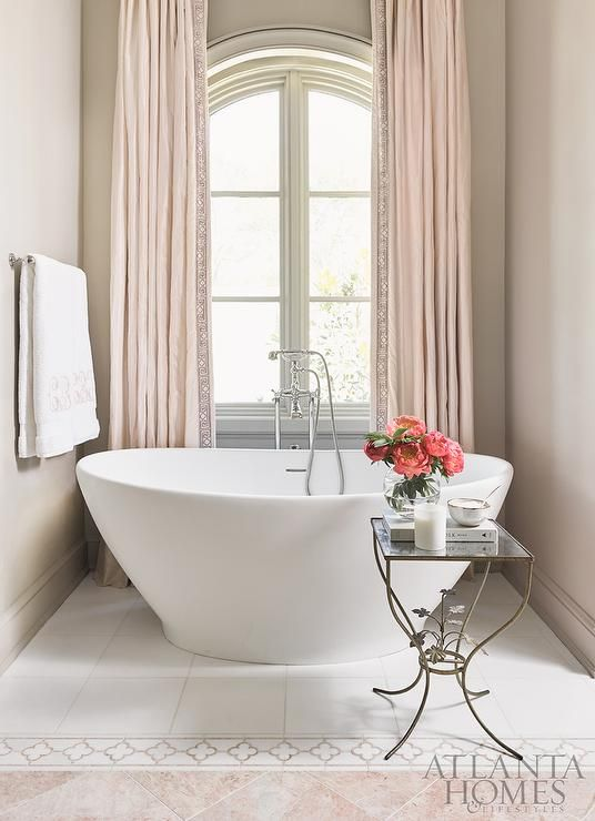 Bathroom walls painted Sherwin Williams Tony Taupe frame an palladian window dressed in long pink curtains located behind a freestanding tub fitted with a polished nickel tub filler and placed on white floor tiles that lead to quatrefoil border tiles lining pink marble diamond pattern tiles.