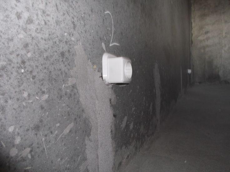 Накладная розетка торчит из стены.