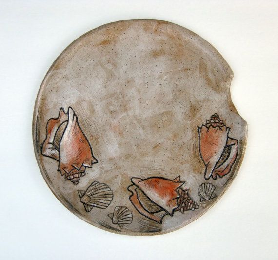 •2016. (10 x 10) This is a hand built stoneware plate depicting several Florida Fighting Conchs, and Calico Scallops, all drawn from shells I found on Sanibel and Captiva Island. •Process: It is made through a technique called Sgraffito. I carve images of the shells into leather hard clay painted with a light coat of white underglaze, then continue working on the images with various other colors. They are fired twice. After the initial firing, I re-work the images with underglaze pencils…