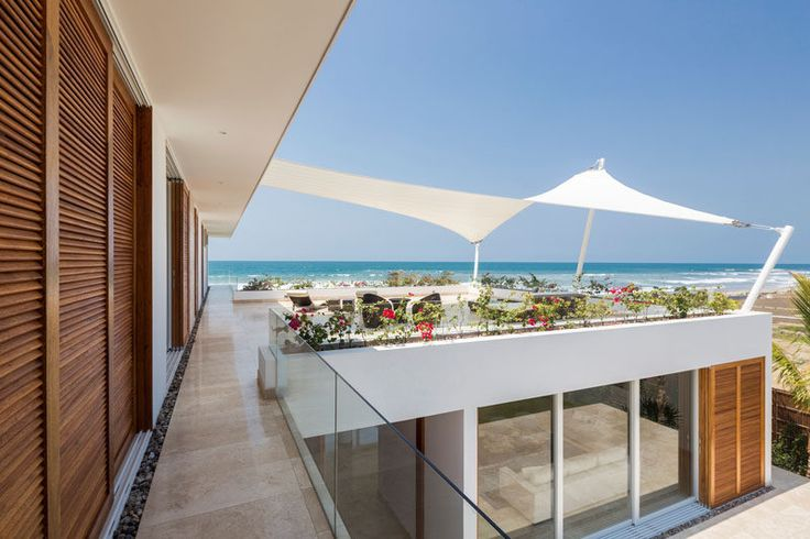 On the upper floor of this modern beach house, there's a covered patio area that's protected from the sun by a shade sail. Simply decorated, plants surround the common area creating the effect of a railing-less deck.