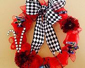 Shabby Chic Nascar racing wreath with checker bow, red and black deco mesh background, rhinestone initial, red accent flowers and miniature race cars! Great for anytime of the year!