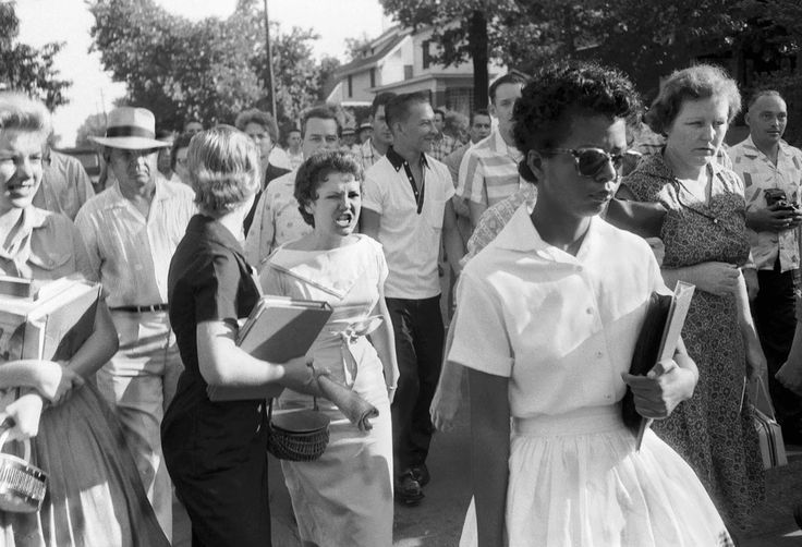 """1957 — Little Rock Nine. In this 1957 picture, Elizabeth Eckford of what became known as """"The Little Rock Nine"""" is seen being followed and threatened by an angry white mob on her way to class, as one of the first African-American students to ever attend classes at Little Rock Central High School in Little Rock, Arkansas."""