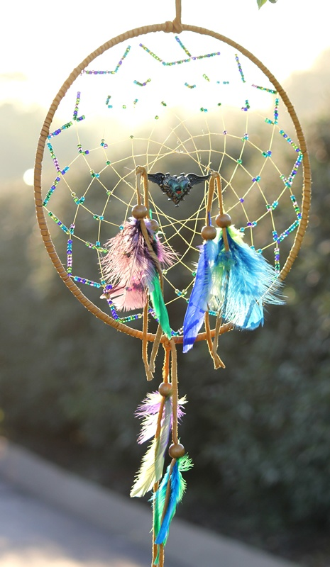 """The Free Spirit Dream Catcher - symbolizes the freedom of the heart and soul to love, dance, live and be happy. This is a 12"""" dream catcher wrapped in soft tan leather, adorned with multi-colored glass beads and feathers - a winged heart pendent hangs in the center."""