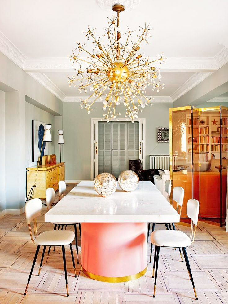 Dining space with mint walls, large white marble table with pink base, white chairs, gold cabinets, and gold chandelier