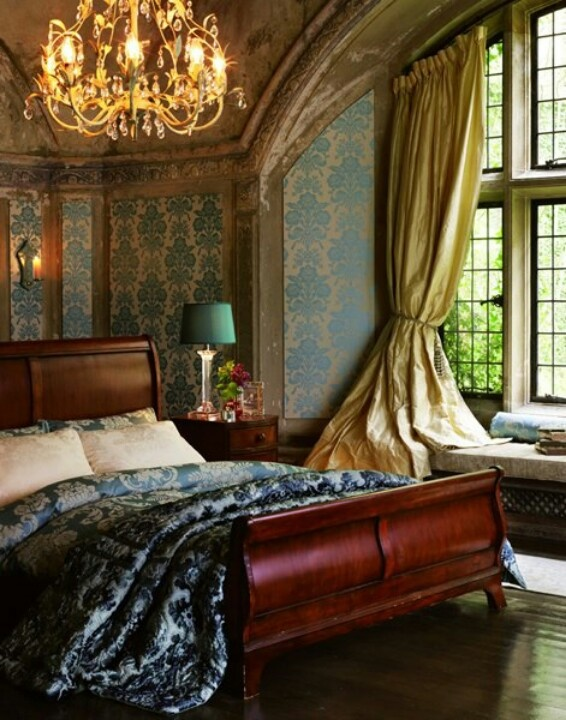 Sleigh bed and tall arched window nook with ornate wall paper and chandelier lovely