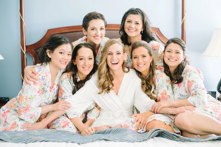 Happy bride with her 6 bridesmaids in matching robes on the bed at the Francis Marion hotel's bridal suite in downtown Charleston, SC.  ***  Aaron and Jillian Photography