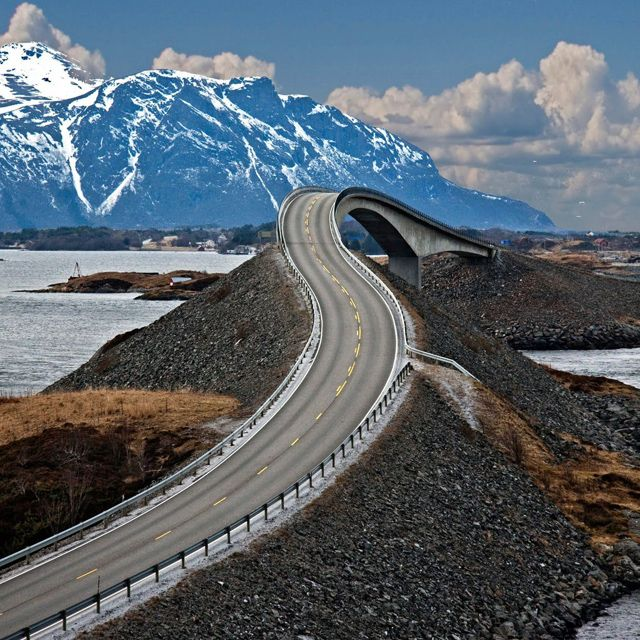 Norway's Storseisundet Bridge -- Architecture and nature combine to create this amazing image of Norway's Storseisundet Bridge. From this perspective, the bridge contorts at an almost surreal angle connecting two land masses together, while overlooking a beautiful mountain range. Surely, this is a sight that's even more impressive when viewed in person.