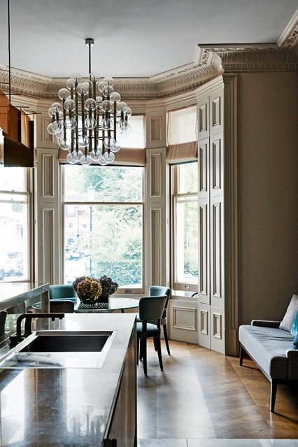 In this period West London house a modern mansion kitchen has been installed wth contemporary lighting, a long island and a dining table. Stylish kitchen design ideas from House & Garden.