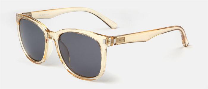 Gafas de sol unisex, de pasta amarillo transparente, con decoraciones metálicas en el frente y lentes polarizadas en color gris.  Entra en multiopticas.com y pruébatelas.