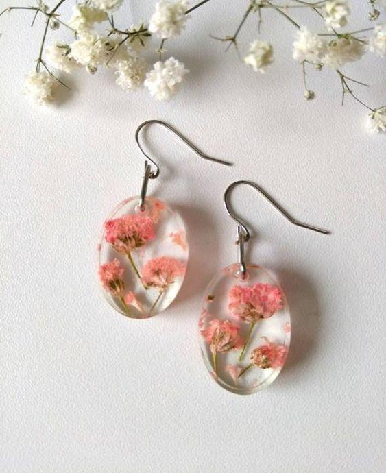 Dangling earrings with silvery metal deer and flower in resin