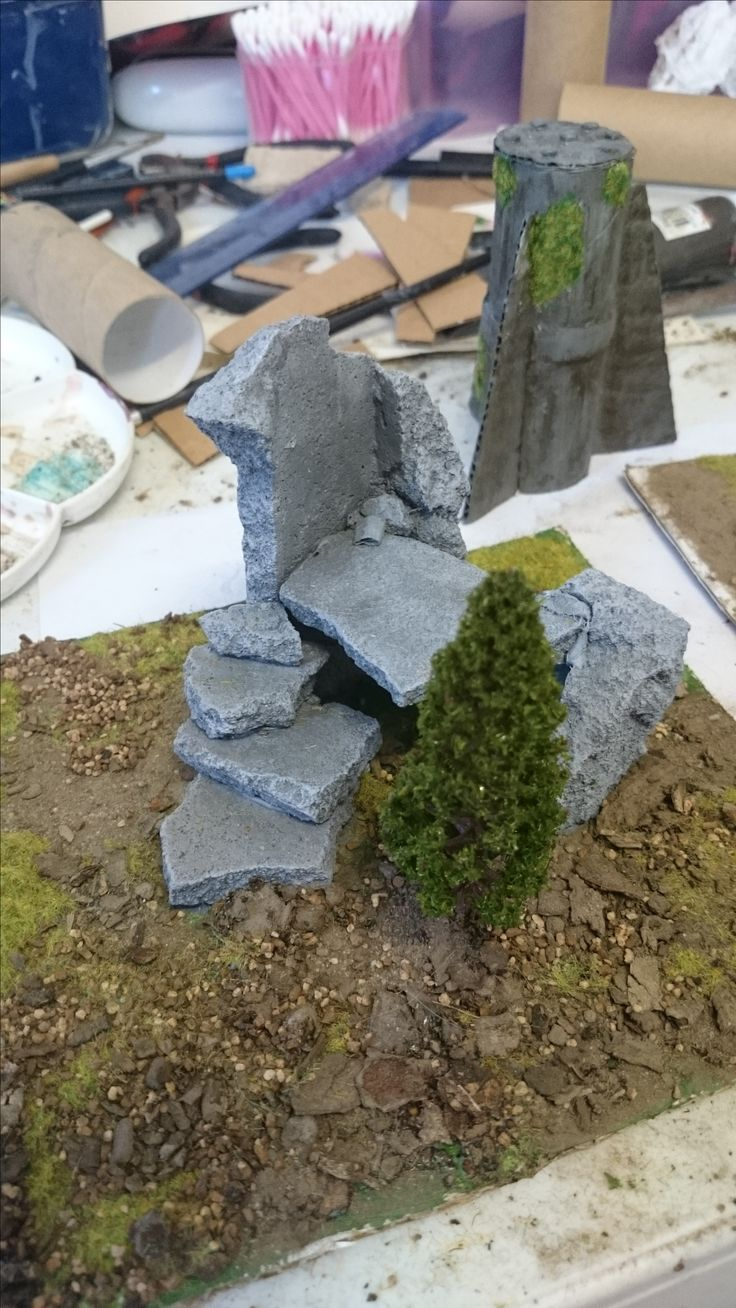 Easy Terrain construction, made with broken cement pieces, painted with grey and white paint. Ground is made from real dirt, stone and tanbark mixture from garden with a sprinkle of fake grass terrain. All glued onto thick bit of cardboard with PVA glue and hot glue gun. Mini tree purchased on ebay in pack.