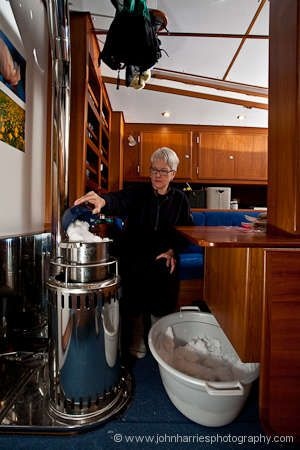 Phyllis melting snow on the Refleks heater on aluminum expedition sailboat Polaris in her winter home at Disko Bay, Greenland