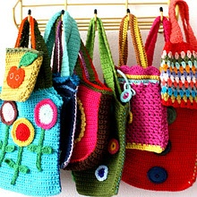 brightly colored bags hanging in a line with white wall behind.