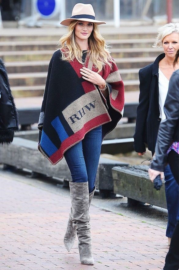 Rosie Huntington-Whitely dons her Burberry Prorsum poncho with a fedora, jeans, and gray suede boots.