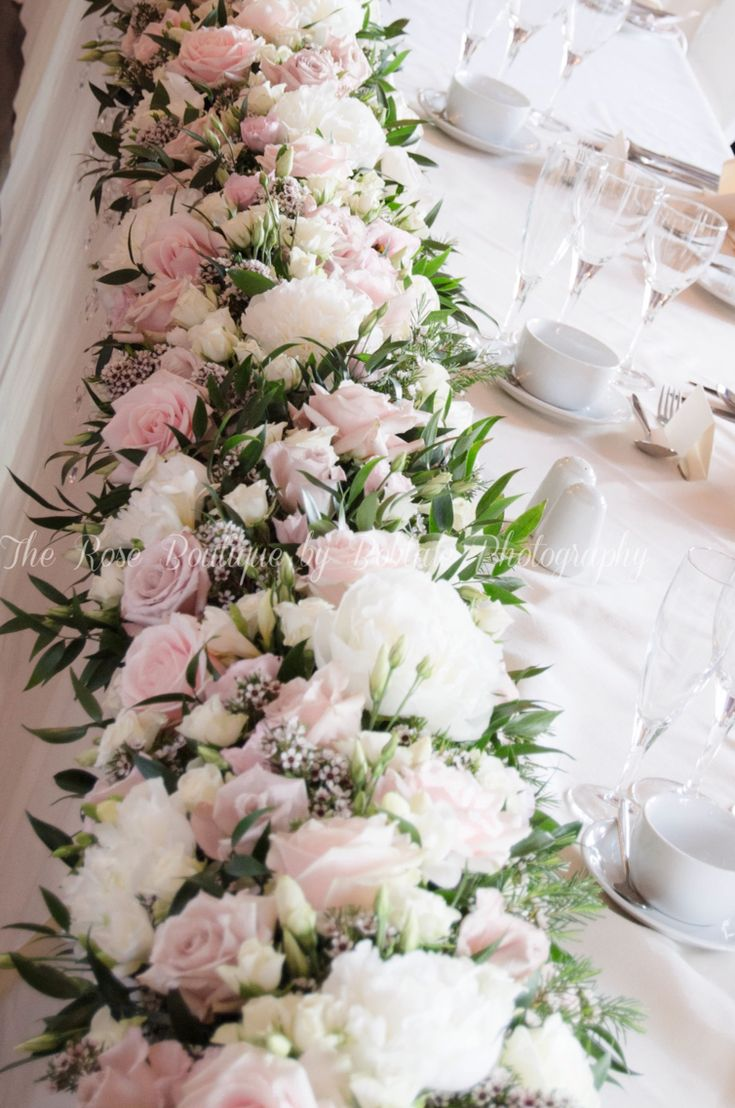 A fabulous bank of flowers running the full length of your top table. Sweet Avalanche roses and peonies. Captured by Bobtale Photography