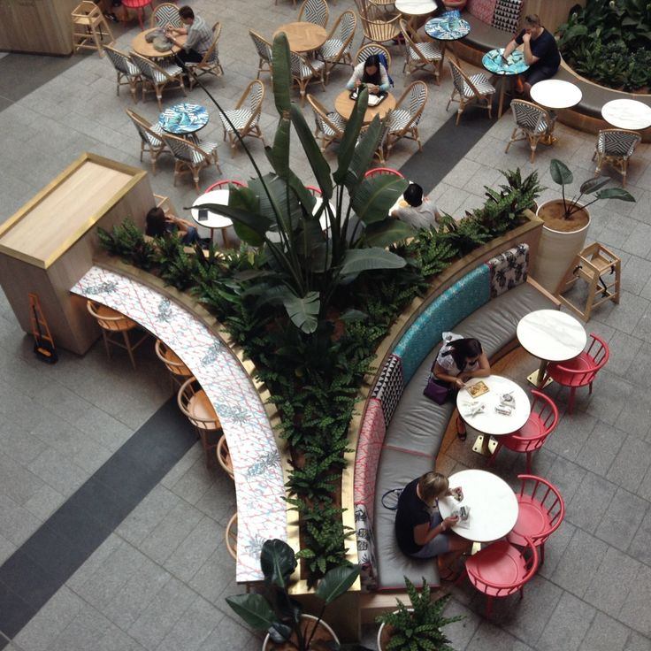 Pacific Fair Food Court - like how the use of curves help divide sections and also provide ifferent types of seating - tables and chairs - bench seating. It also adds as a statement piece with the beautiful greenery in the middle