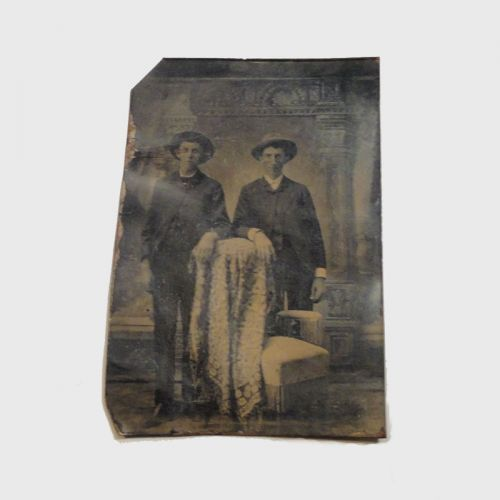 Antique Photograph - Tintype Image of a two men wearing hats standing side by side, one arm resting on a blanket covered chair