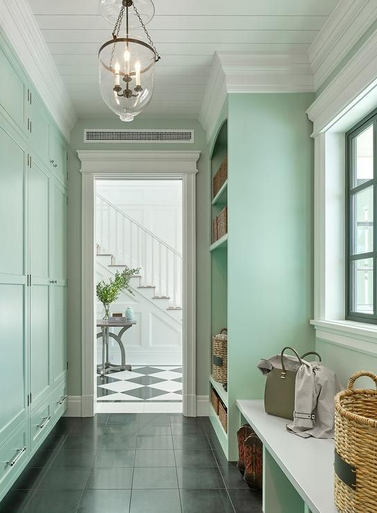 Welcoming mint green mudroom features a glass bell jar lantern hung from a white shiplap ceiling in front of mint green closed lockers located above drawers accented with polished nickel pulls.