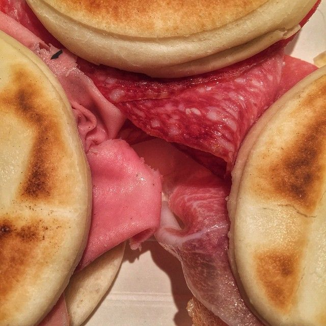 Lunchtime snack in Bologna - traditional Tigelle bread from the Modena area stuffed with Mortadella, Prosciutto Crudo, and Salami - Instagram by ourtastytravels