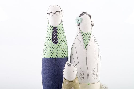 Family portrait - mother father and toddler dressed in shades of sage green and mint and navy blue .Timo Handmade eco dolls