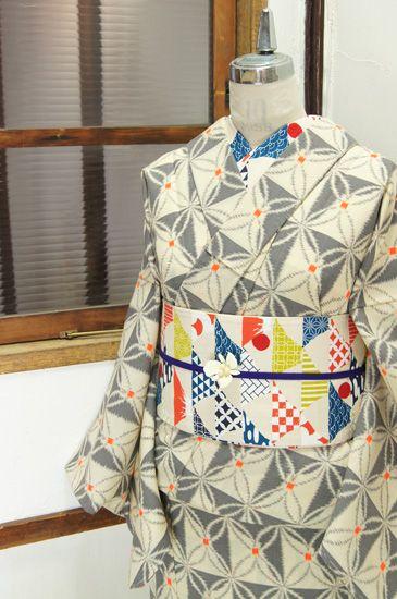 """クリームホワイトにグレーの七宝デザインが重ねられたウールの単着物です。 """"クリームホワイトとグレーのモノクロームでデザインされたトライアングルパターンもスタイリッシュな格子に、赤のドットがアクセントになった七宝デザインが重ねられたアートでモダンなウールの単着物です。"""""""