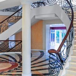 www.trabczynski.com ST490 Dwustronne policzkowe schody gięte montowane na wylewce betonowej. Policzki z malowanego dębu, balustrada z ręcznie kutej stali z drewnianym pochwytem. Stopnice kamienne. Realizacja w prywatnej rezydencji, Projekt – TRĄBCZYŃSKI.