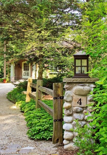 Lake Michigan Cabin Makeover | Midwest Living | Stone pillars and split-rail fencing enhance the rustic setting.