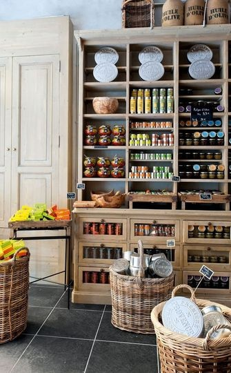 Epicerie gourmande à Nice. Big baskets on the floor tiled flora with lighter cupboards reaching roof