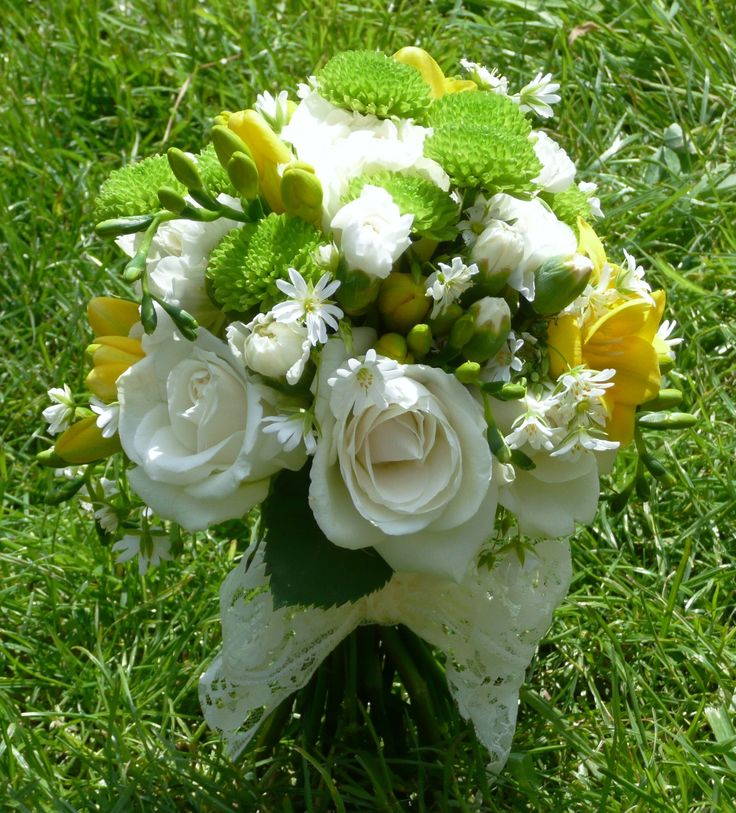 Country-garden combination of white roses, yellow freesia, hand-tied bridal bouquet bound with lace. Perfect for a vintage barn or garden wedding. Florissimo, Shropshire