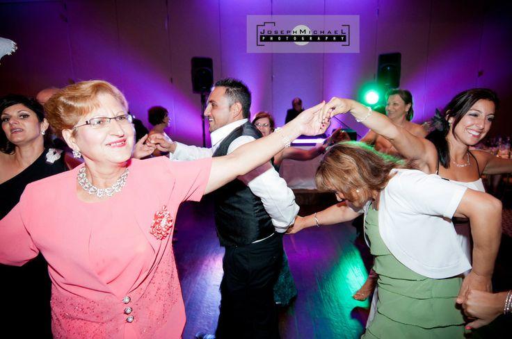 La Primavera Wedding Photos, greek wedding, orthodox greek dancing, holding hands dancing.