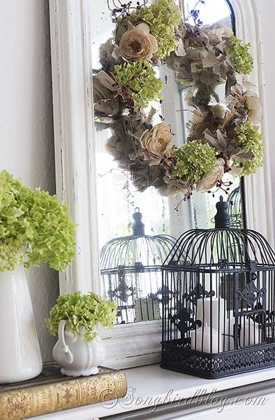 Fall mantel decoration with a wreath on a vintage French mirror, bird cages, vintage books and hydrangea flowers. Via http://www.songbirdblog.com (2)