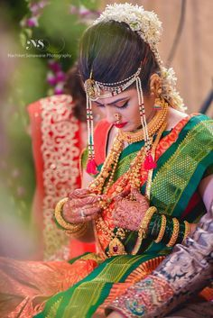 An orange and green navaari silk saree with detailed, green woven border, styled with a thushi necklace. Stunning Maharashtrian bride!