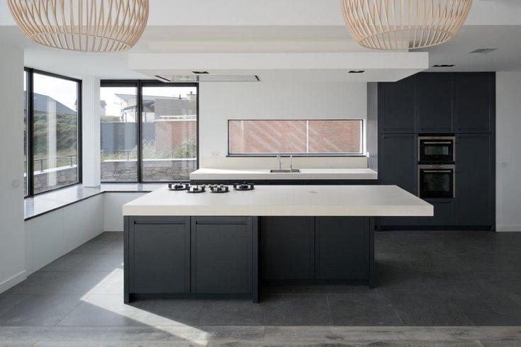 Moderne zwart-wit keuken met kookeiland en inbouwapparatuur. Het 'envelop raam' boven aanrecht zorgt voor een bijzondere verbinding met de tuin. Ontwerp: Bloem en Lemstra Architecten Amsterdam
